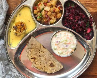 Portion Control Meal Plate: Methi Pakora kadhi, Beetroot Poriyal, Kabuli Chana & Raw Mango Salad, Mixed Millet Phulka & Cucumber & Onion Raita